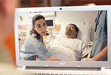 A clinician cares for a patient at the bedside.